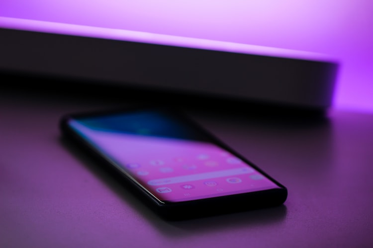 A smartphone bathed in purple light