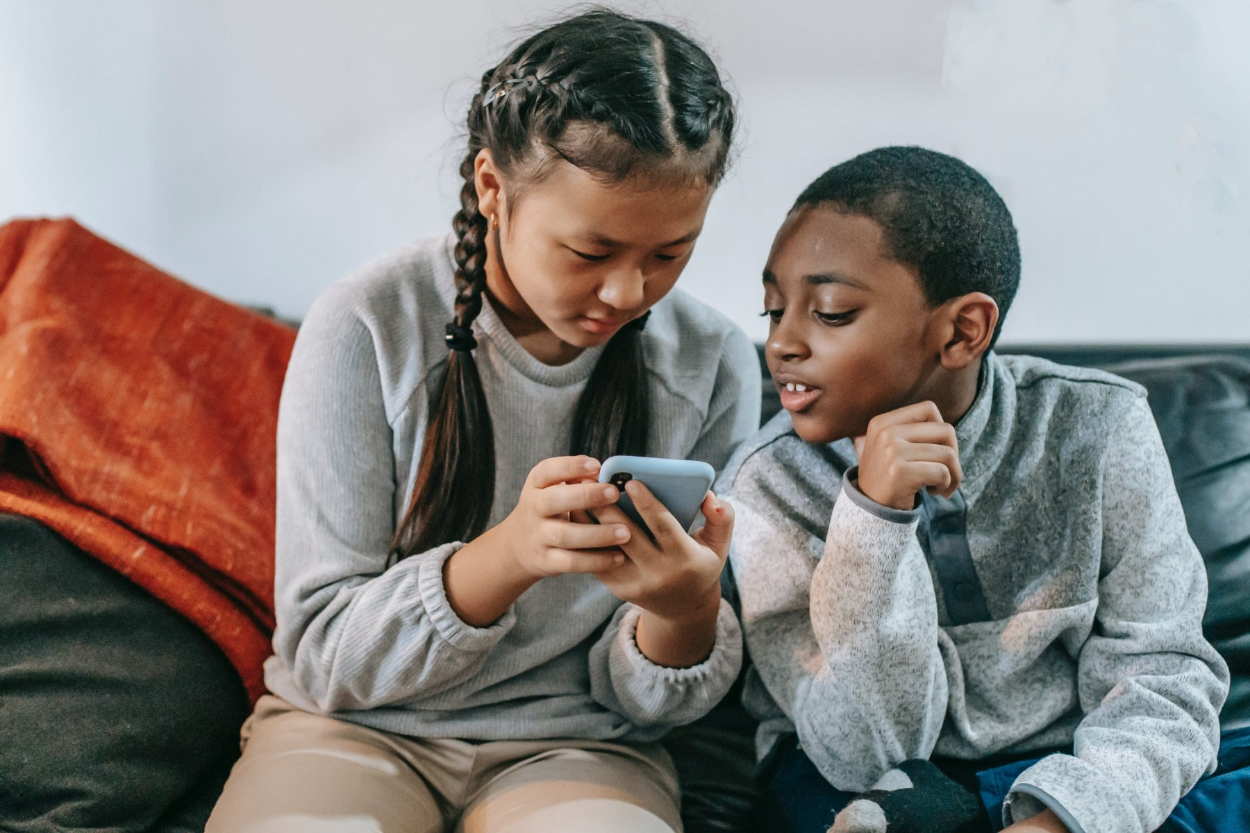 Two children looking at a phone
