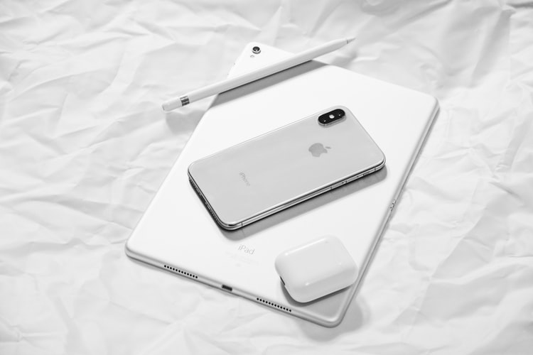 White Apple products including an iPhone, AirPods, Mac and Pen