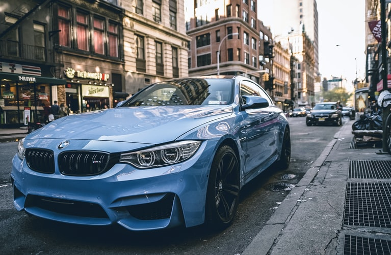 A blue BMW car in a city