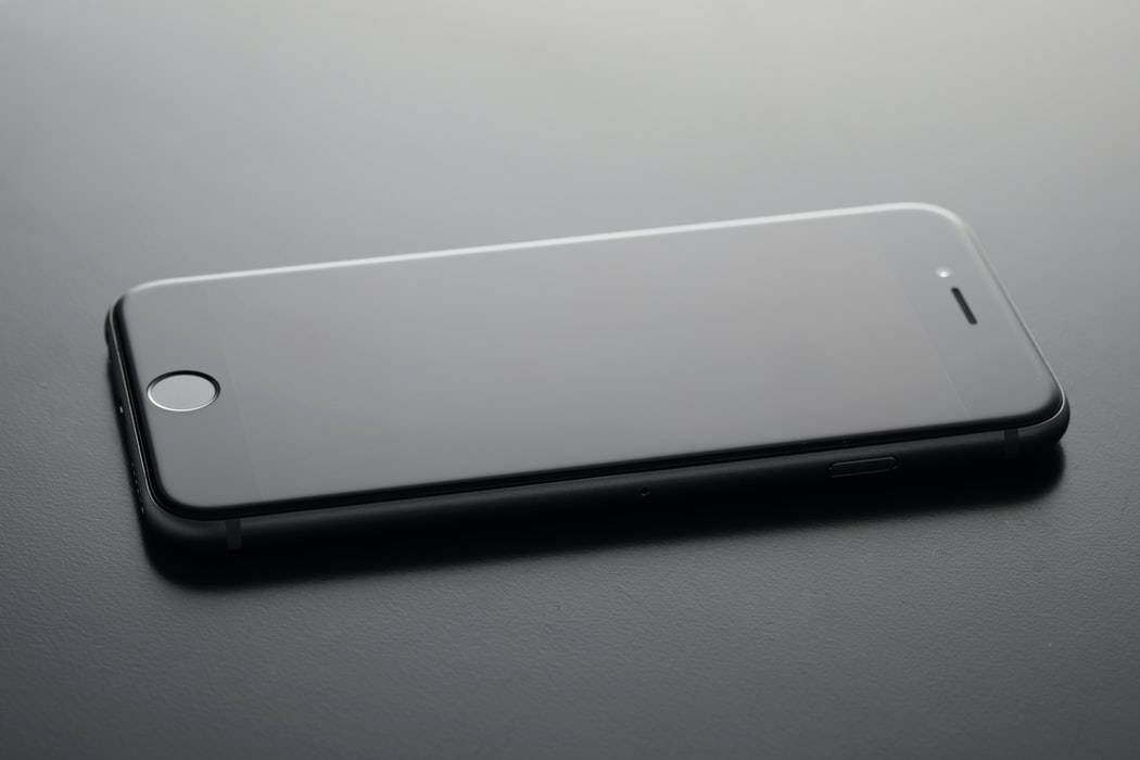 A black iPhone with its screen turned off against a black background