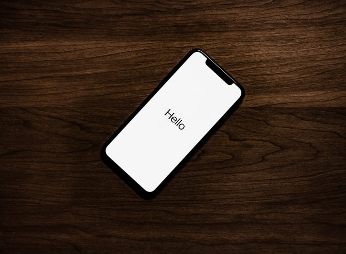 An iPhone on a wooden table with a hello white screensaver