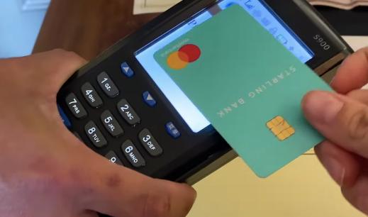 Person scanning starling bank card at checkout