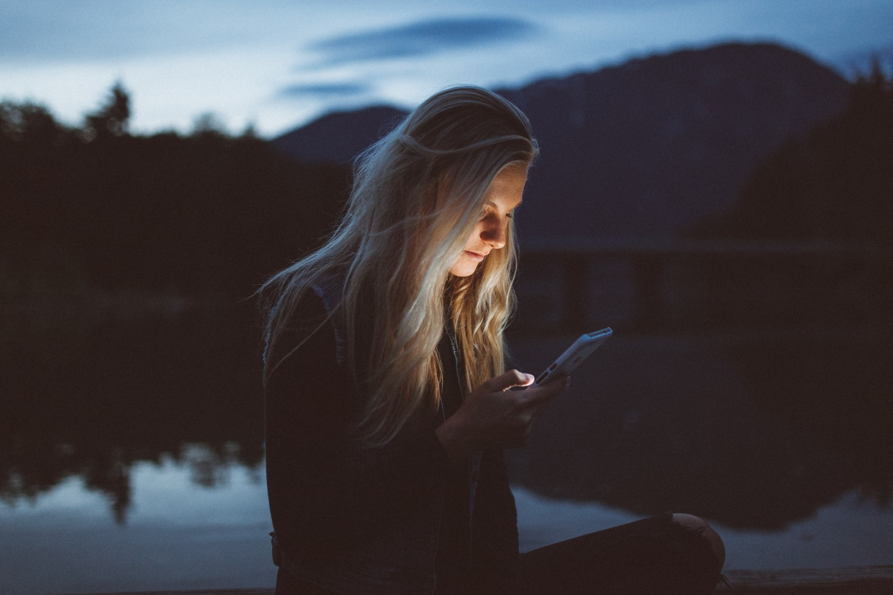 A woman using her phone at night
