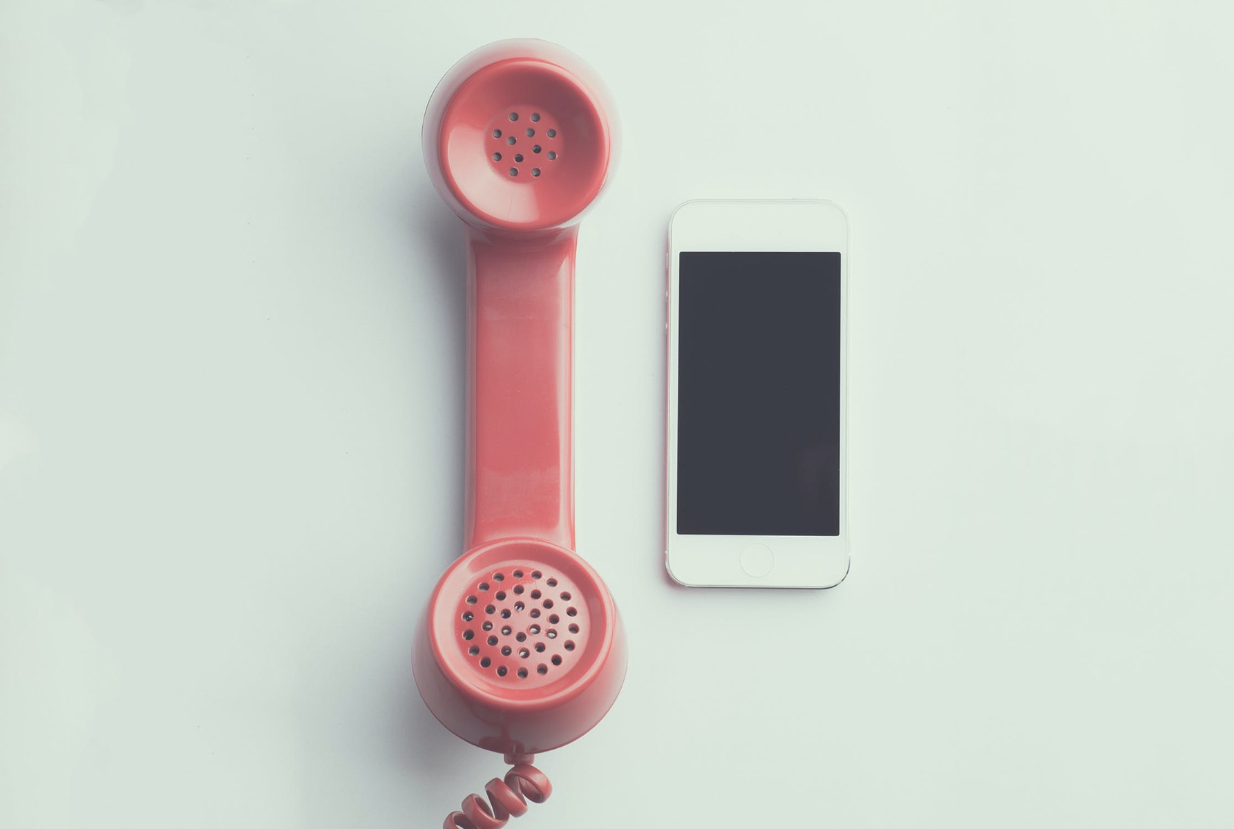 An old red phone next to an iPhone