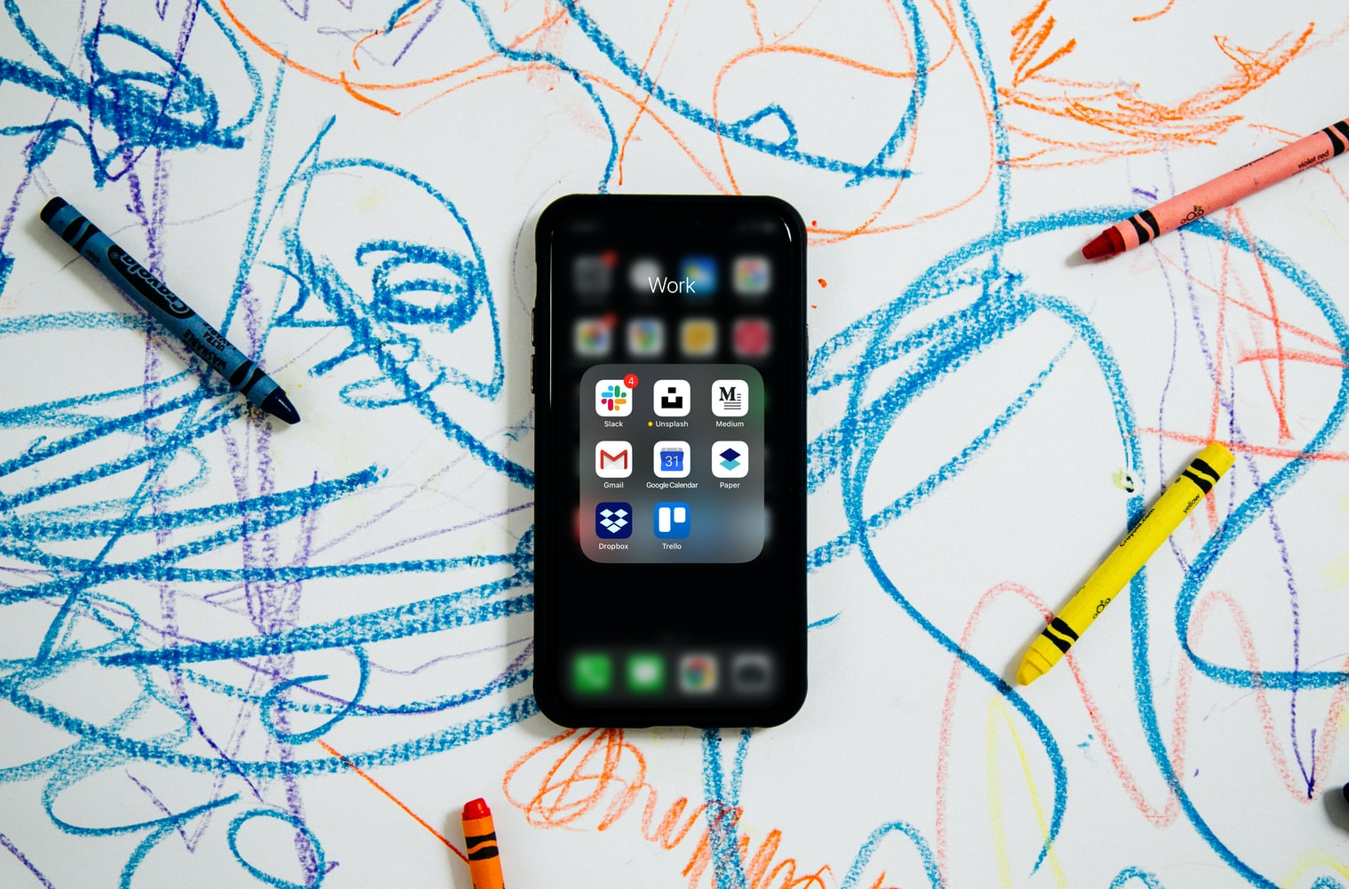 An iPhone surrounded by crayon scribbles